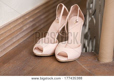 Pair of elegant and stylish brides biege shoes on floor