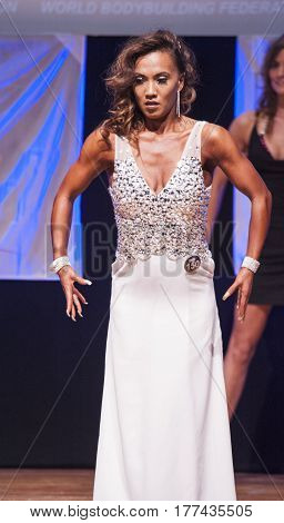 MAASTRICHT THE NETHERLANDS - OCTOBER 25 2015: Female fitness model Esther Blom in evening dress shows her best physique in championship on stage at the World Grandprix Bodybuilding and Fitness of the WBBF-WFF
