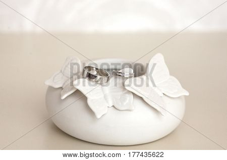 Beautiful silver wedding rings on tender, white porcelain figure with butterfly