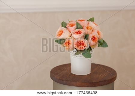 Wedding decorating bouquet of pink roses and green petals, in vhite vase, standing small round table