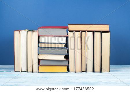 Book stack hardback colorful books on wooden table and blue background. Back to school. Copy space for text. Education concept