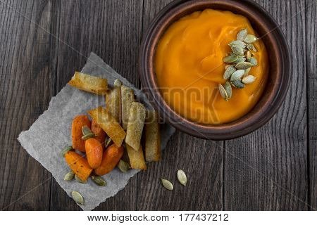 Pumpkin cream soup in a clay bowl with snack fried croutons bread,baked carrots.