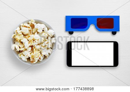 Popcorn smartphone and 3d anaglyph glasses on white table