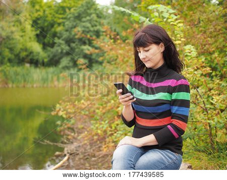 Beautiful Young Woman Using Smartphone At Autumn Park. Pretty Young Woman In Autumn Clothes Sending