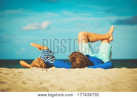 father and little son play on tropical beach