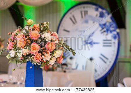 Gorgeous bouquet of roses and other flowers on guest table on wedding ceremony, with clock on a background