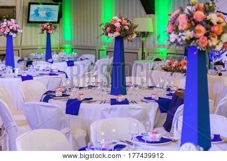 Beautifully decorated in blue and white colours wedding hall with guests tables with bouquets on pedestals on them