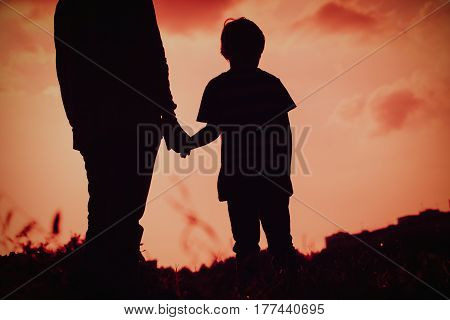 silhouette of father and son holding hands at sunset nature