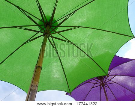 Two vibrant colored parasols, one green and one purple against sunny blue sky, Thailand