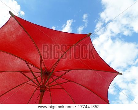 One red colored sunshade against vivid blue sky and fluffy white clouds