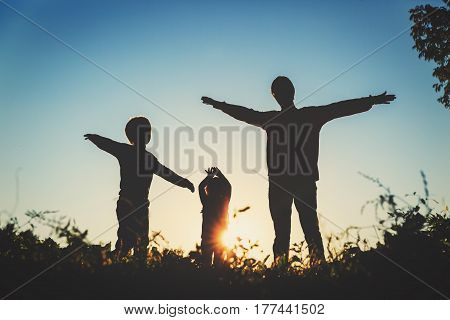 father with son and daughter silhouettes play in sunset nature