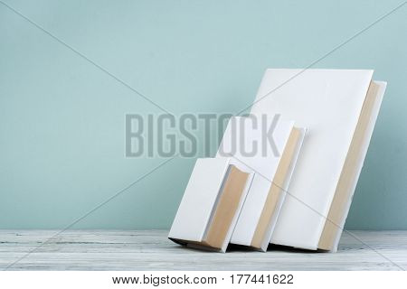 Book stack hardback books on wooden table and blue background. Back to school. Copy space for text. Education concept