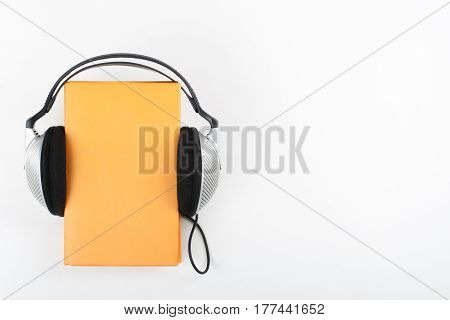 Audiobook on white background. Headphones put over yellow hardback book empty cover copy space for ad text. Distance education e-learning concept