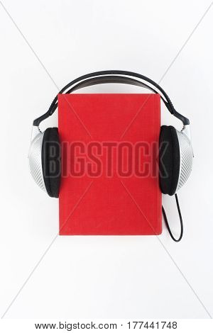 Audiobook on white background. Headphones put over blue hardback book empty cover copy space for ad text. Distance education e-learning concept