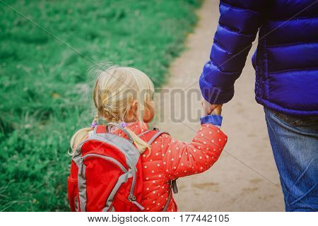 father walking little daughter to school or daycare, education and learning