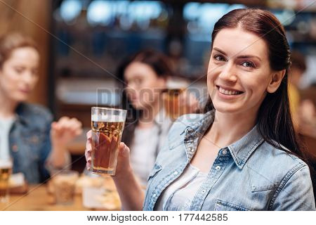 Just Friday. Positive delighted woman holding bocal of beer in right hand looking straight on camera while having weekend party
