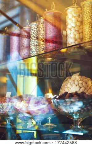 Rich variety of chocolates and candies in big glass jars in display window of italian pastry shop in the street of Florence at sunny day