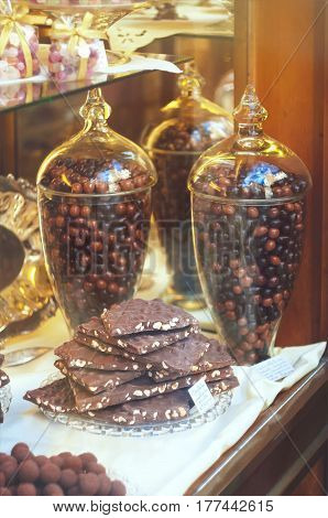 Rich variety of chocolates in big glass jars and candies in display window of italian pastry shop at sunny day