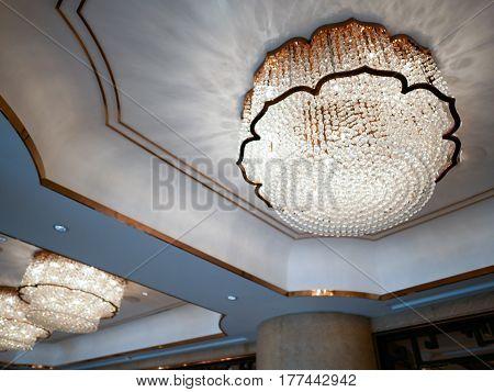 Huge crystal glass chandeliers hanging on a ballroom