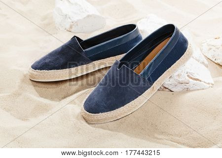 Pair of sports shoes on sand or beach