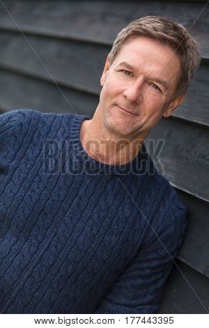 Portrait shot of an attractive, successful handsome and happy middle aged man male outside wearing a blue sweater