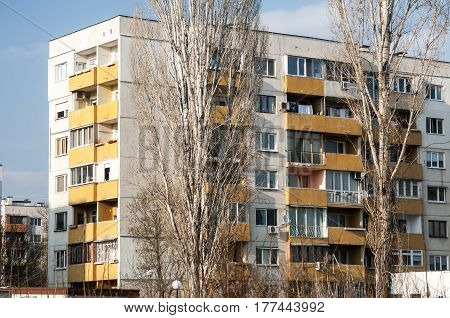 Obsolete residential building on blue sky background in sunny day