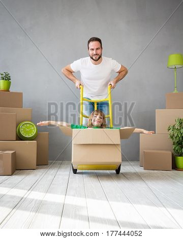 Happy family playing into new home. Father and child having fun together. Moving house day and express delivery concept