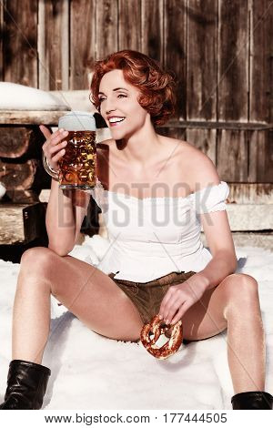 Young red-haired woman sitting in a short leather trousers in the snow with pretzel and mug.