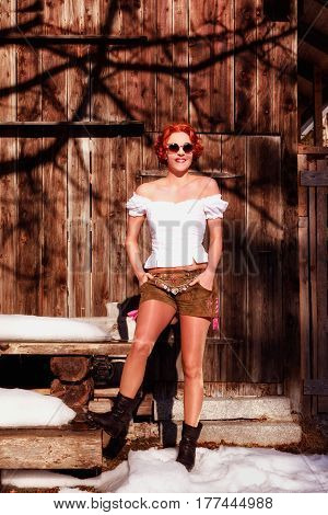 Portrait of a beautiful redhead Bavarian woman with cowl blouse a shorts made from leather and sunglasses