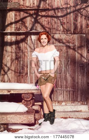 Portrait of a beautiful redhead Bavarian woman with shoulder-free blouse and a shorts from Leder.
