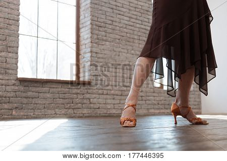 Step by step. Confident gifted aging woman dancing in the ballroom while performing dancing steps and having training session