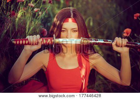 Asian woman holding samurai sword near face sitting in flower poppy field in red dress.