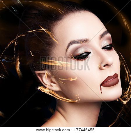 Beauty sexy vampire woman with dripping blood on her mouth over black background