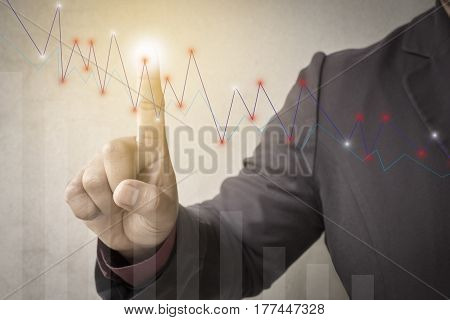 business man fingers with the graphics the status of business growth. investment success and profitable business concepts.Forex graph on background.