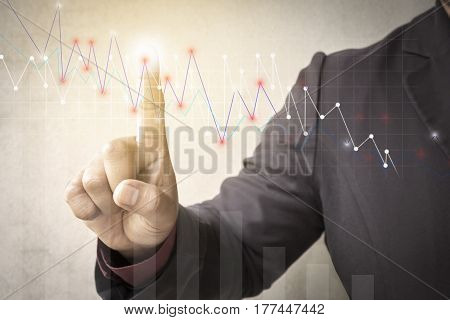 business man fingers with the graphics the status of business growth. investment success and profitable business concepts.