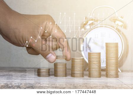 Man hand stacking coins with clock background . Business Finance and Money conceptSave money for prepare in the future . / productivity growth concept