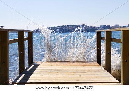 Muelle recibiendo golpe de olas de mar.