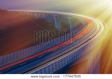 Blurred lights of vehicles driving on viaduct long exposure sunlit with golden morning rays. Transportation on the road connectivity and rush hour concept background with copy space.