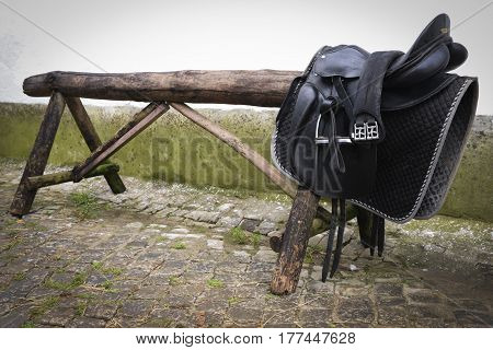 Black leather horse saddle holded in a trunk