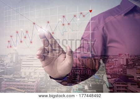 Double exposure of business man fingers with the graphics, the status of business growth. investment, success and profitable business concepts.