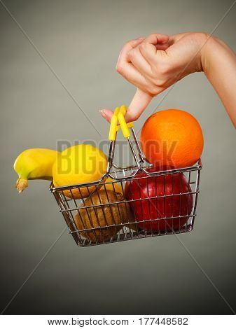 Buying healthy food vegetarian gluten free vegan products. Woman hand holding shopping cart with fruits inside