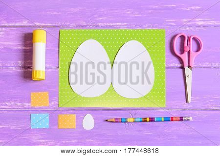 How to make Easter egg greeting card. Step. Tutorial. Colored cardboard sheets, template in shape of egg, scissors, glue stick, pencil on a wood table. Kids Easter paper crafts idea. Top view. Closeup