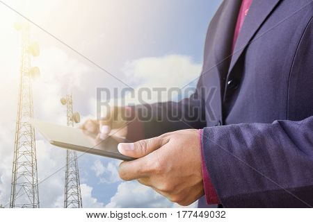 Businessman holding tablet at work telecom network with blue sky with sunshine background concept telecommunication in business and development .