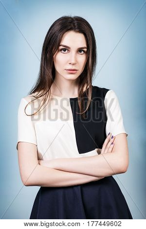 Serious young woman with crossed hands over blue background