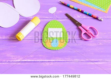 Easter greeting card with egg made of colored cardboard, colored cardboard sheets, scissors, paper templates in form of eggs, glue stick, pencil on a wood table. Easy children paper crafts for Easter