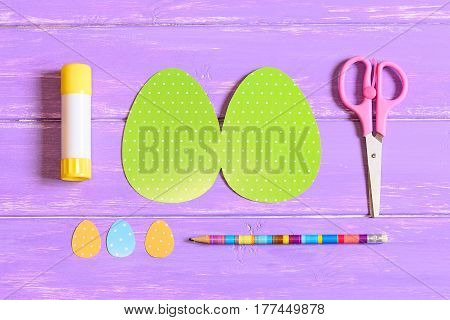 How to make Easter egg greeting card. Step. Guide. Colored cardboard pieces in shape of egg, scissors, glue stick, pencil on a wooden table. Children Easter paper crafts idea. Top view. Closeup