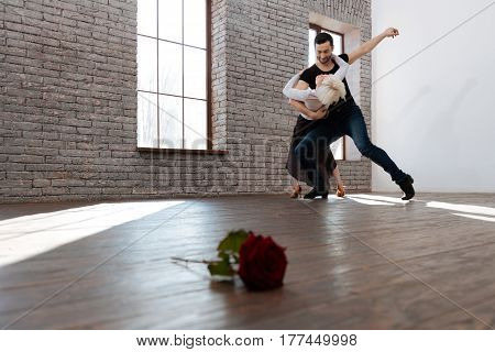 Performing flexible steps together. Skilled flexible experienced dance instructor teaching senior woman tango while dancing and learning new step