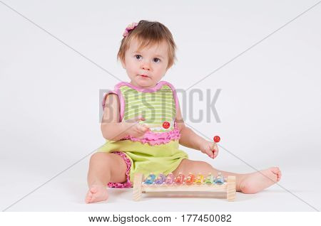 Girl with excitement playing on a xylophone isolated on white.