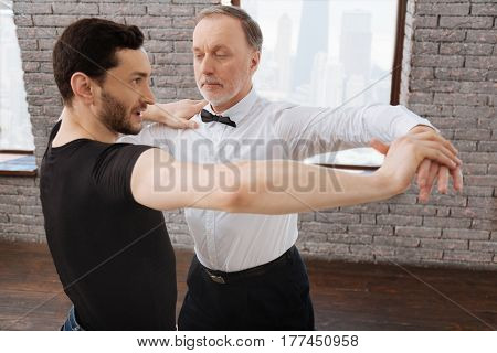 Improving dance technique. Charismatic helpful experienced dance couch tangoing with senior man while having training session and teaching new dance step