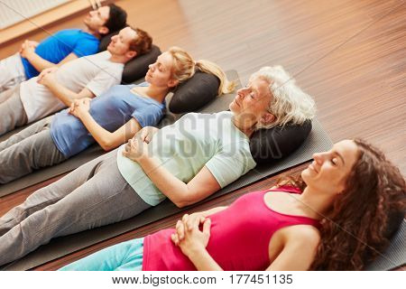 Senior with a group meditating at fitness center